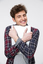 Happy man hugging laptop over gray background Stock Photography