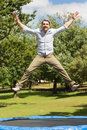 Happy man jumping high on trampoline in park Royalty Free Stock Photos
