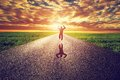 Happy man jumping on long straight road, way towards sunset sun Royalty Free Stock Photo