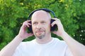 Happy man listening music outdoors in wireless headset Royalty Free Stock Photo