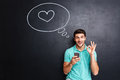 Happy man in love using smartphone sign over chalkboard Royalty Free Stock Photo