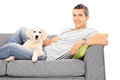 Happy man lying on couch with a puppy isolated white background Stock Photos