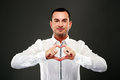 Happy man making heart from his hands on black background Stock Photography