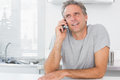 Happy man making phone call in kitchen sitting at counter Royalty Free Stock Image