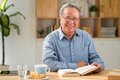 Happy man mature asian with a book sitting at table Stock Photo