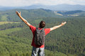 Happy man on mountain with hands up Stock Photo