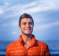 Happy man outdoors portrait of handsome active young adult in orange jacket Stock Photo