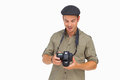 Happy man in peaked cap holding camera on white background Royalty Free Stock Photo