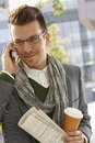 Happy man on phone call outdoors young businessman talking mobile holding newspaper and coffee Royalty Free Stock Images