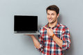 stock image of  Happy man in plaid shirt pointing on blank screen laptop