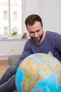 Happy man planning his next vacation bearded sitting on a sofa with a large globe looking at world destinations Royalty Free Stock Photos