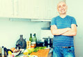 Happy man in the prime of life in kitchen prepared salads Royalty Free Stock Photo