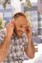 Happy man putting in earbuds smiling outdoors Stock Photo
