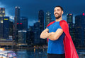 Happy man in red superhero cape over night city Royalty Free Stock Photo