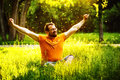 A happy man is relaxing on green grass with squint eyes and raised up to sky arms at sunny summer day at park background concept Stock Photos