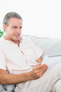 Happy man relaxing on his couch using tablet pc at home in living room Stock Image