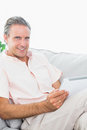 Happy man relaxing on his couch using tablet pc looking at camer camera home in living room Royalty Free Stock Images
