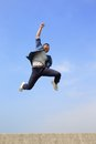 Happy man run and jump college student with blue sky background full length asian male Royalty Free Stock Images
