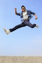Happy man run and jump college student with blue sky background full length asian male Royalty Free Stock Photo