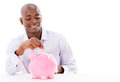 Happy man saving money in a piggybank isolated over white Royalty Free Stock Images