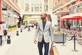 Happy man with shopping bags walking on a street Royalty Free Stock Photo