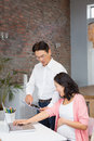 Happy man showing tablet to his pregnant wife men at home Royalty Free Stock Image