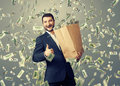 Happy man showing thumbs up excited businessman standing under dollar s rain and Royalty Free Stock Photos