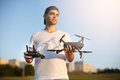 Happy man shows You small compact drone and remote controller. Pilot holds quadcopter and RC in his hands.