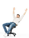 Happy man sits on the chair and raised hands up Stock Photo