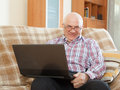 Happy man sitting on couch with laptop elderly gray haired working at his sofa at home Royalty Free Stock Photography