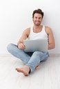 Happy man sitting on floor with laptop Royalty Free Stock Photo