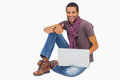 Happy man sitting on floor using laptop giving thumbs up white background Royalty Free Stock Image