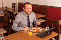 Happy man sitting in restaurant with laptop Royalty Free Stock Photo