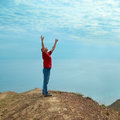 Happy man standing cliff hands up looking sea Stock Photo