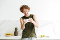 Happy man standing at the kitchen and play games by phone. Royalty Free Stock Photo