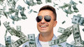 Happy man in sunglasses with falling dollar money