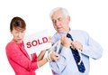 Happy man taking away sad woman closeup portrait of strange couple excited old to have tying hands girl holding sold sign isolated Royalty Free Stock Photography