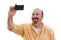 Happy man taking a self portrait on his mobile or selfie phone to send to friends over the social media network holding the Royalty Free Stock Images
