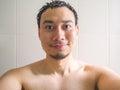 Happy man taking selfie in bathroom.