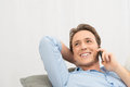 Happy man talking on phone young mobile lying sofa Stock Image