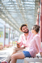 Happy man talking to woman while sitting on bench under shade men women Stock Image