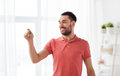 Happy man touching something imaginary at home