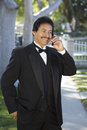 Happy Man In tuxedo Using Cell Phone At Quinceanera Stock Photo