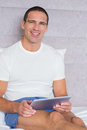Happy man using his tablet pc sitting on bed smiling at camera at home in the bedroom Royalty Free Stock Images