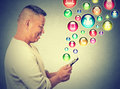 Happy man using texting on smartphone social media application icons flying up Royalty Free Stock Photo