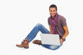 Happy man wearing scarf sitting on floor using laptop white background Royalty Free Stock Photo