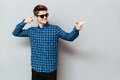 Happy man wearing sunglasses pointing. Royalty Free Stock Photo