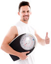 Happy man with a weight scale and thumbs up isolated over white Stock Photography