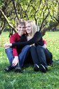 Happy man and woman embrace and sit on green grass Stock Image