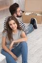 Happy man and woman sitting on the floor tired preparing to relocate to new apartment. Royalty Free Stock Photo